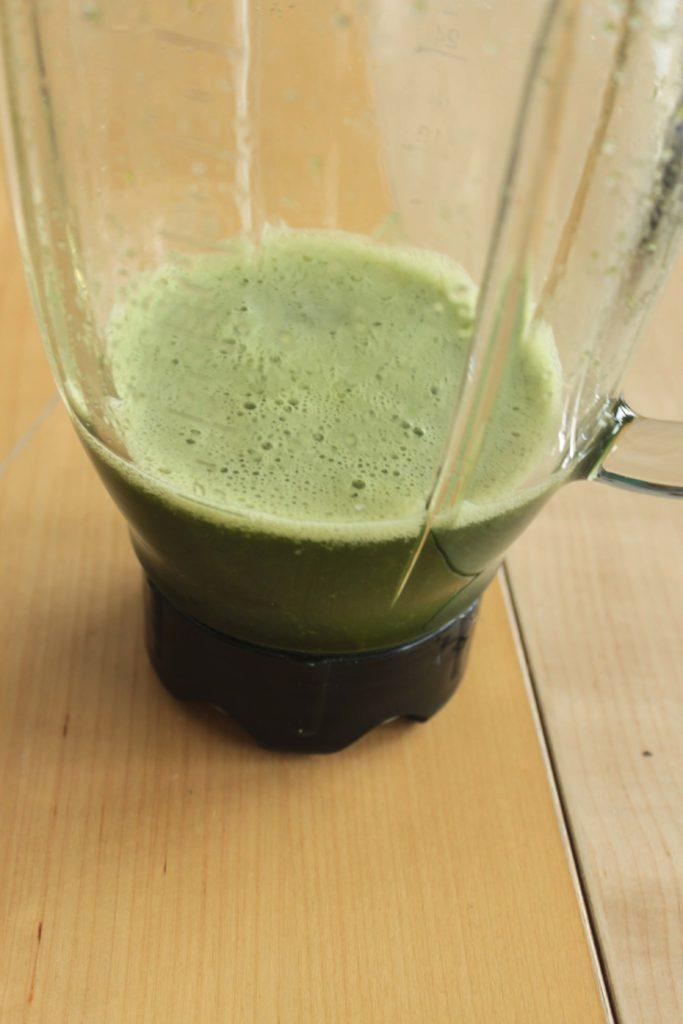 Basilic mixé dans un blender qui donne un jus vert.