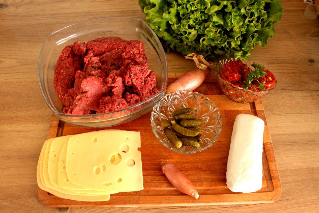 Ingrédients du hamburger tomate mozzarella basilic avec de la viande hachée, de la mozzarella, de l'emmental, des échalotes, de la salade et des tomates séchées marinées