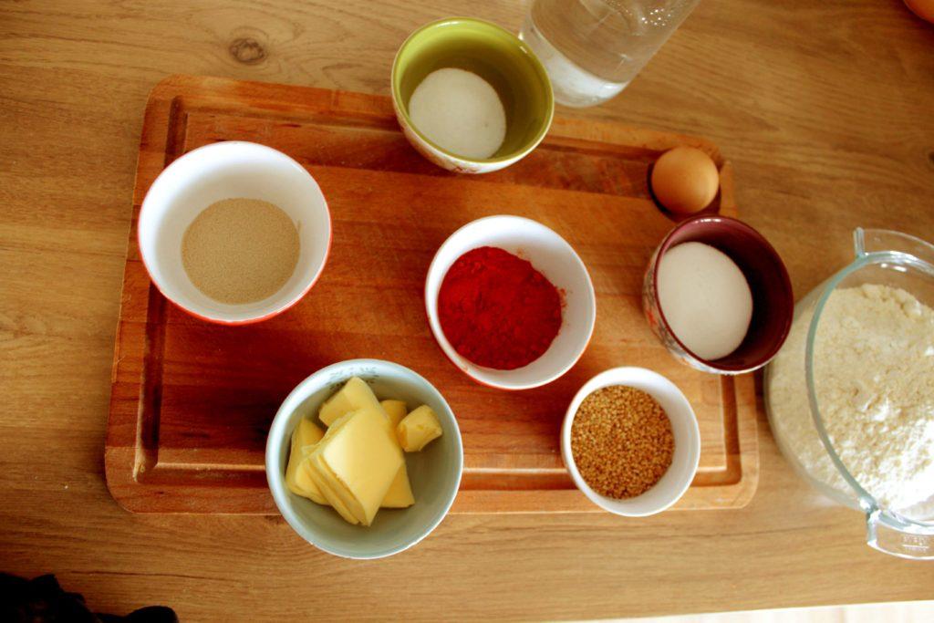 Ingrédients du pain rouge au paprika avec de la farin, du beurre, de la levure, du sucre, du sel, un oeuf, et du paprika