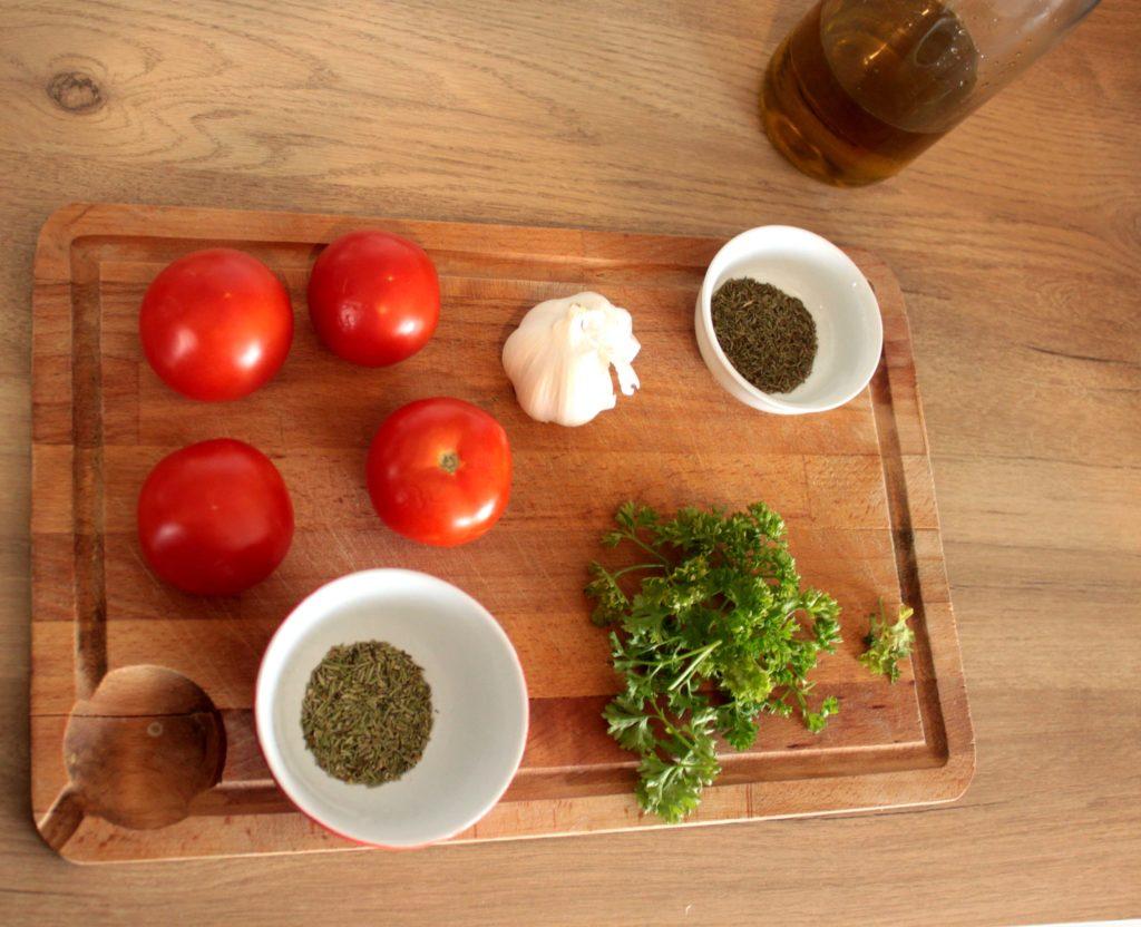 Ingrédients pour les tomates séchées et marinées. Des tomates, du thym, du romarin, de l'ail, de l'huile d'olive, du persil