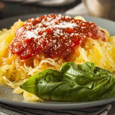 Une courge spaghetti avec une sauce bolognaise et du basilic