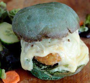 Un hamburger au poisson frit avec un bun bleu et du fromage fondu