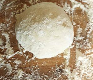 Un paton de pâte à pizza fraichement pétri avec de la farine autour
