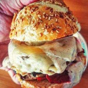 Un burger végétarien avec une galette végétale, du fromage et de la sauce au fromage blanc