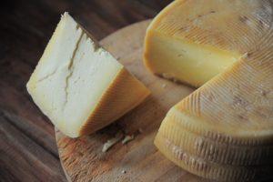 Une meule de fromage avec un morceaux coupée