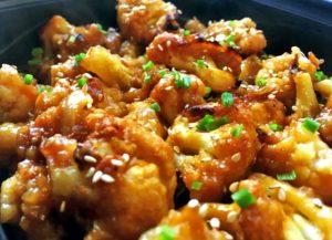 Du chou fleur façon poulet kun pao mariné dans du soja et saupoudré d'oignons nouveaux et sésame