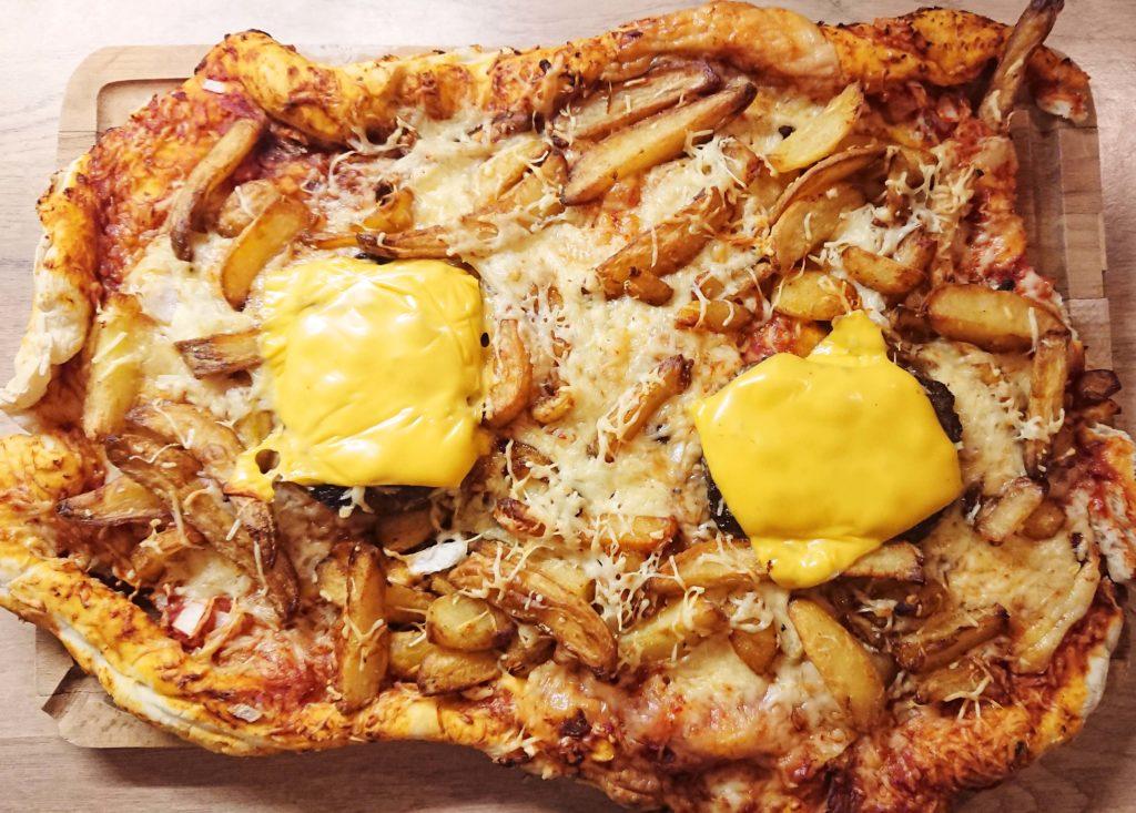 Une pizza hamburger, avec des steak haché, des frites, et du fromage qui fond par dessus le tout.